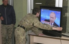 Troops from the Donetsk People's Republic watch Vladimir Putin on TV. Photo: Reuters.