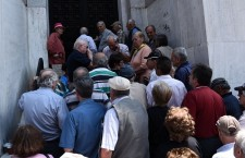While Greece's bank are ordered to shut down for a full week, pensioners storm shuttered bank branches throughout the country, leading to scenes of chaos. Photo: Giannis Papanikos/AP