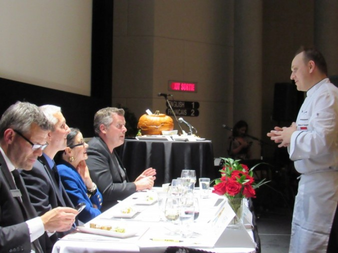 Zsolt Varga presenting his meal to a panel of judges at the 2015 Embassy Chef Challenge, held at Victoria Hall, in the John F. Diefenbaker building. Photo: C. Adam.