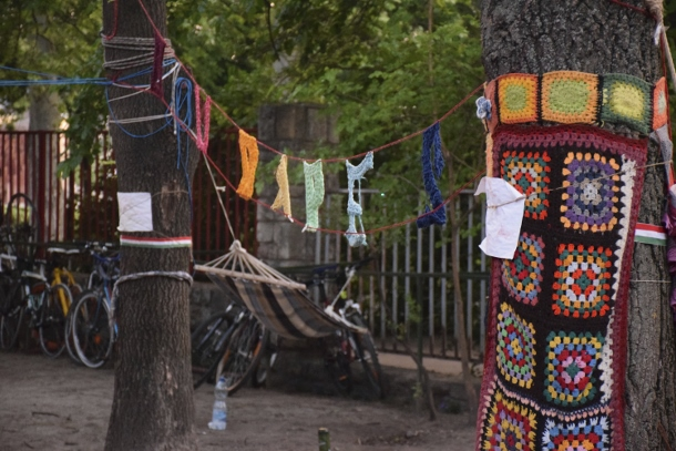 "Artists decorate the camp and trees, spelling out ""Budapest"" in a crochet sign. Photo Credit: Colby Hopkins"