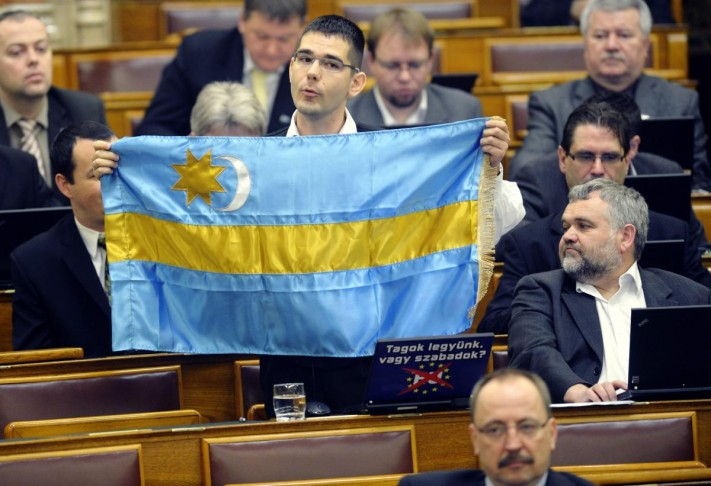 Far Right Jobbik Party MPs are demonstrating with the Szekler Flag in the Hungarian Parliament during session.