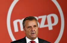 Gyula Molnár standing in front of the MSZP logo.